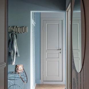 На фото: маленькая узкая прихожая в современном стиле с синими стенами, светлым паркетным полом, одностворчатой входной дверью, белой входной дверью и коричневым полом