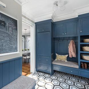 Inspiration pour une entrée traditionnelle de taille moyenne avec un vestiaire, un mur gris, un sol en bois brun et un sol noir.