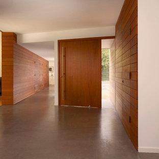 サンフランシスコの広い片開きドアモダンスタイルのおしゃれな玄関ロビー (コンクリートの床、木目調のドア、茶色い壁) の写真