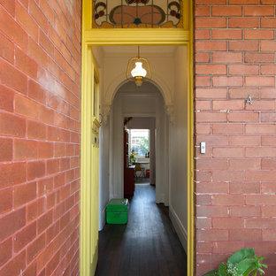 Eklektisk inredning av en liten ingång och ytterdörr, med en gul dörr, en enkeldörr, vita väggar och mörkt trägolv