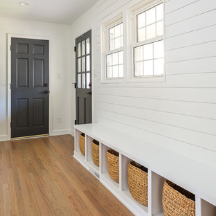 Large trendy light wood floor and brown floor entryway photo in Raleigh with white walls and a black front door