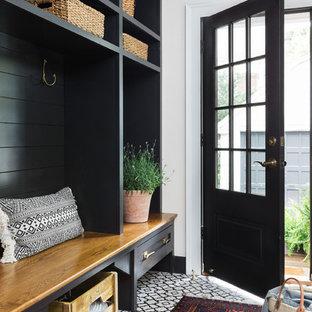 Diseño de vestíbulo posterior de estilo de casa de campo, de tamaño medio, con paredes blancas, suelo de baldosas de cerámica y puerta negra