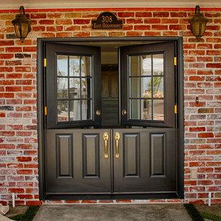 Bild på en stor vintage ingång och ytterdörr, med bruna väggar, en tvådelad stalldörr och en vit dörr