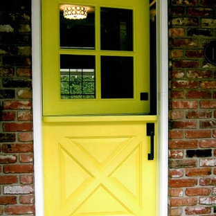 Example of a mid-sized transitional brick floor and brown floor entryway design in Orange County with a yellow front door
