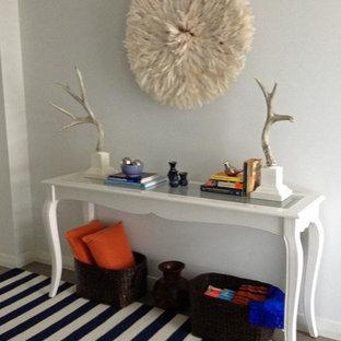 Ispirazione per un corridoio moderno di medie dimensioni con pareti bianche, pavimento in gres porcellanato, una porta a pivot e una porta bianca