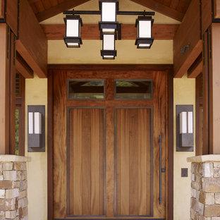 Modelo de puerta principal contemporánea con puerta de madera en tonos medios, paredes beige, suelo de piedra caliza, puerta pivotante y suelo beige