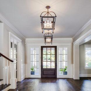 Идея дизайна: огромное фойе в морском стиле с бежевыми стенами, темным паркетным полом, одностворчатой входной дверью, входной дверью из темного дерева, коричневым полом, кессонным потолком и деревянными стенами