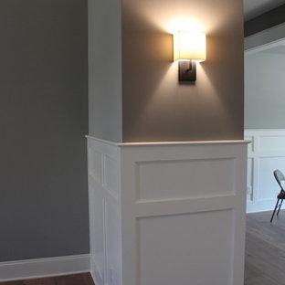 Стильный дизайн: фойе среднего размера в стиле модернизм с серыми стенами, паркетным полом среднего тона, одностворчатой входной дверью и черной входной дверью - последний тренд