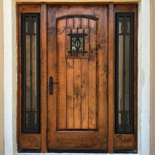 Réalisation d'une porte d'entrée chalet de taille moyenne avec un mur beige, une porte simple et une porte en bois foncé.