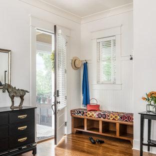 Cette image montre une entrée craftsman avec un vestiaire, un mur blanc, un sol en bois brun, une porte simple et une porte blanche.