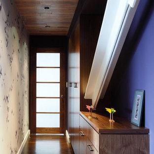 Idéer för funkis hallar, med lila väggar, mörkt trägolv, en enkeldörr och glasdörr