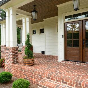 Свежая идея для дизайна: входная дверь в стиле кантри с белыми стенами, двустворчатой входной дверью, входной дверью из дерева среднего тона и красным полом - отличное фото интерьера
