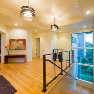 Inspiration pour un grand hall d'entrée design avec un mur beige, un sol en bois clair, une porte simple et une porte en verre.