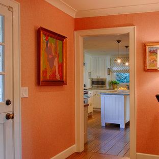 Inspiration pour un petit hall d'entrée bohème avec un mur orange, un sol en bois foncé, une porte hollandaise et une porte noire.