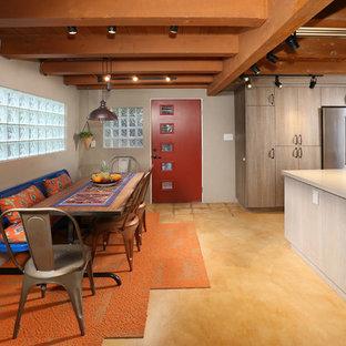 ロサンゼルスの広い片開きドアサンタフェスタイルのおしゃれな玄関 (コンクリートの床、赤いドア、グレーの壁) の写真