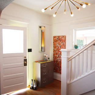 Small eclectic medium tone wood floor entryway photo in Portland with white walls and a white front door