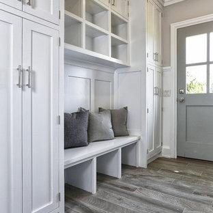 Mittelgroßer Maritimer Eingang mit Stauraum, weißer Wandfarbe, hellem Holzboden, Einzeltür, grauer Tür und grauem Boden in New York