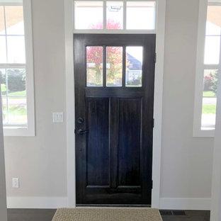Idée de décoration pour une porte d'entrée craftsman de taille moyenne avec un mur beige, un sol en vinyl, une porte simple, une porte en bois foncé et un sol marron.