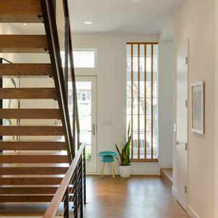 Cette photo montre une porte d'entrée rétro avec un mur blanc, un sol en bois clair, une porte simple et une porte blanche.