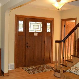 Ispirazione per una porta d'ingresso stile americano di medie dimensioni con pareti beige, pavimento in legno massello medio, una porta singola e una porta in legno scuro