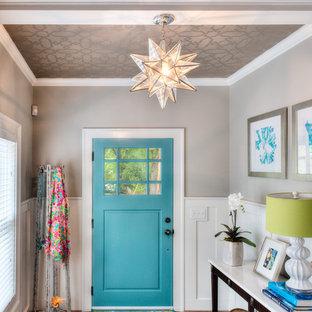 Idee per un piccolo ingresso chic con pareti grigie, pavimento in legno massello medio, una porta singola e una porta blu