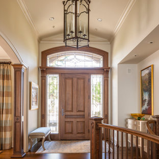 Идея дизайна: фойе среднего размера с бежевыми стенами, паркетным полом среднего тона, одностворчатой входной дверью, входной дверью из дерева среднего тона, коричневым полом и сводчатым потолком