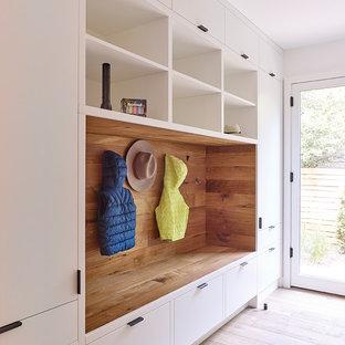 Ispirazione per un grande ingresso con anticamera minimal con pareti bianche, pavimento in legno massello medio, una porta singola, una porta bianca e pavimento marrone