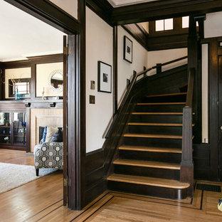 サンフランシスコの中サイズの片開きドアトラディショナルスタイルのおしゃれな玄関ロビー (白い壁、無垢フローリング、濃色木目調のドア、ベージュの床) の写真