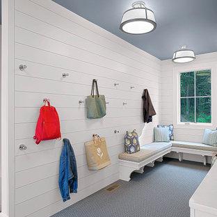 Inredning av ett klassiskt stort kapprum, med vita väggar, heltäckningsmatta och blått golv
