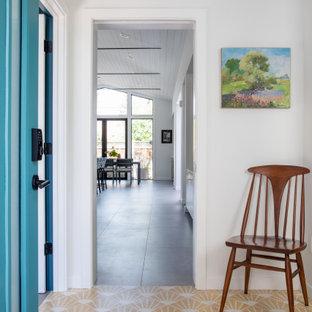 Идея дизайна: фойе среднего размера в стиле ретро с белыми стенами, бетонным полом, одностворчатой входной дверью, синей входной дверью и желтым полом