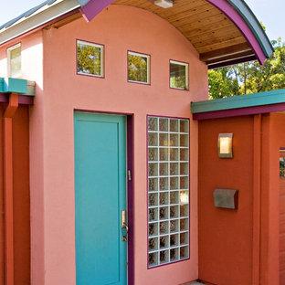 Ejemplo de puerta principal bohemia con paredes rosas, suelo de cemento, puerta simple, puerta azul y suelo gris