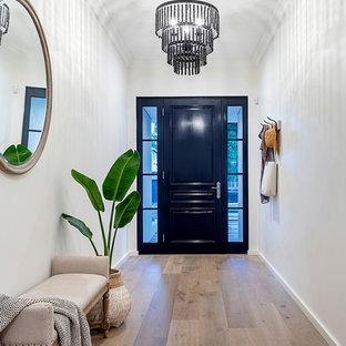 Foto på en vintage foajé, med vita väggar, mellanmörkt trägolv, en enkeldörr, en svart dörr och brunt golv