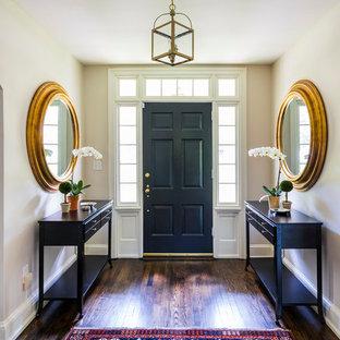 Klassisk inredning av en stor foajé, med beige väggar, mörkt trägolv, en enkeldörr, en svart dörr och brunt golv