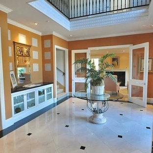 Großer Klassischer Eingang mit Foyer, oranger Wandfarbe, Porzellan-Bodenfliesen und weißem Boden in Los Angeles