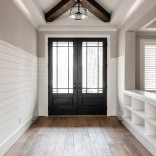 Rustikaler Eingang mit beiger Wandfarbe, braunem Holzboden, freigelegten Dachbalken und Holzdielenwänden in Charlotte