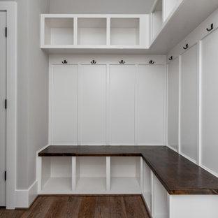 Exemple d'une entrée craftsman avec un vestiaire, un mur beige, un sol en bois brun et boiseries.