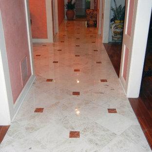 Неиссякаемый источник вдохновения для домашнего уюта: большое фойе в классическом стиле с оранжевыми стенами, мраморным полом и двустворчатой входной дверью