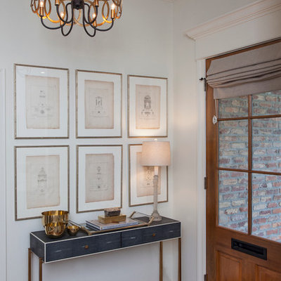 Example of a transitional dark wood floor entryway design in New Orleans with white walls and a medium wood front door