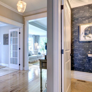 Example of a mid-sized transitional medium tone wood floor and beige floor entryway design in Other with gray walls and a glass front door