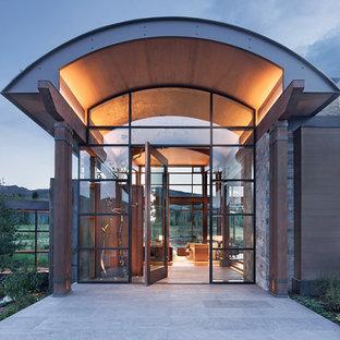На фото: огромная входная дверь в стиле рустика с поворотной входной дверью и стеклянной входной дверью с