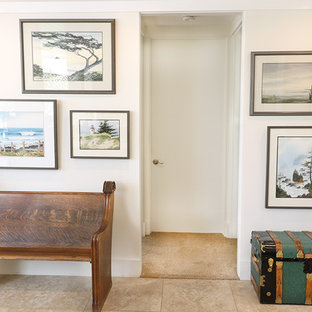Example of a mid-sized classic limestone floor and beige floor foyer design in Orange County with white walls