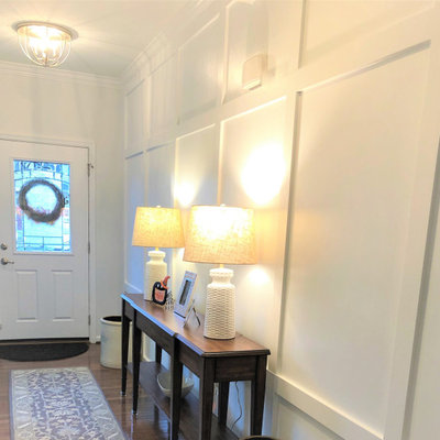 Example of a mid-sized transitional medium tone wood floor and wainscoting foyer design in Baltimore with white walls