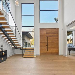 Idées déco pour une très grand porte d'entrée contemporaine avec un mur blanc, un sol en bois clair, une porte simple, une porte en bois brun et un sol beige.
