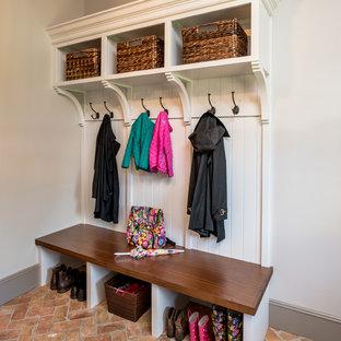 Idéer för ett stort klassiskt kapprum, med grå väggar, tegelgolv, en enkeldörr, en brun dörr och rött golv