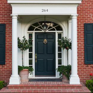 Foto på en stor vintage ingång och ytterdörr, med röda väggar, tegelgolv, en enkeldörr och en svart dörr