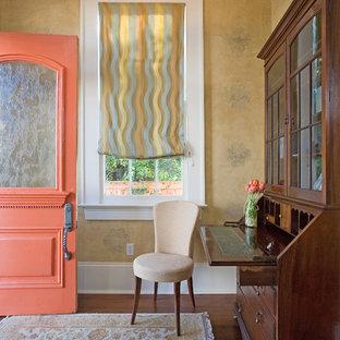 Klassisk inredning av en entré, med gula väggar, mörkt trägolv, en enkeldörr och en orange dörr