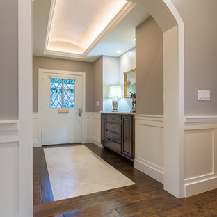 Example of a mid-sized classic medium tone wood floor entryway design in Austin with beige walls and a white front door