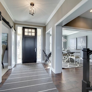 Example of a large transitional dark wood floor entryway design in Minneapolis with gray walls and a black front door