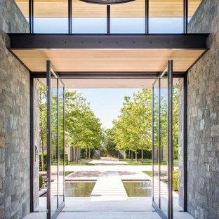 Esempio di un ampio ingresso minimalista con una porta a pivot e una porta in metallo