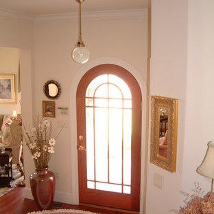 他の地域の中サイズの片開きドアトラディショナルスタイルのおしゃれな玄関ドア (無垢フローリング、木目調のドア、ピンクの壁) の写真